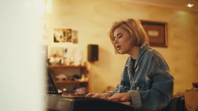 vídeos de stock, filmes e b-roll de a garota toca piano e canta dentro de casa. uma mulher cria música e uma canção. o artista se apresenta no pianoforte. um músico compõe uma melodia. um adolescente está praticando em um instrumento. - música acústica