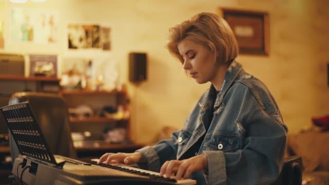 vidéos et rushes de la jeune fille joue du piano et chante à l'intérieur. une femme crée de la musique et une chanson. l'artiste se produit au pianoforte . un musicien compose une mélodie. un adolescent pratique sur un instrument. - synthétiseur