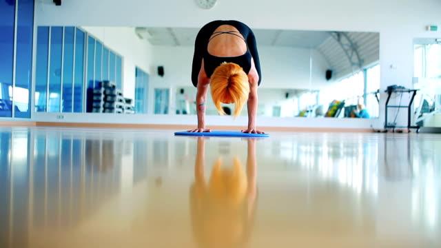 das mädchen, das yoga in der turnhalle des sports praktiziert - haarfarbe stock-videos und b-roll-filmmaterial