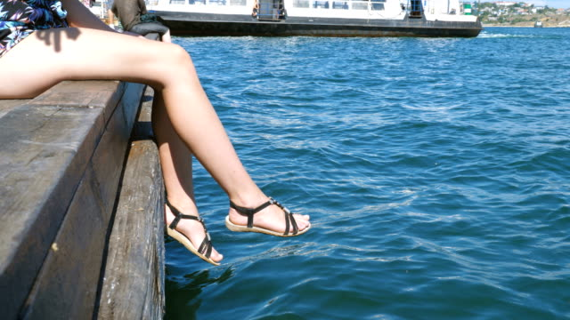 The girl relaxes sitting on a wooden pier.