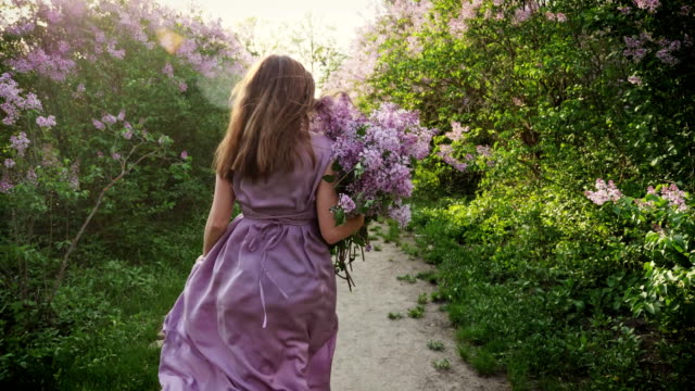 vídeos de stock e filmes b-roll de the girl runs along with a bouquet of lilacs - violeta flor