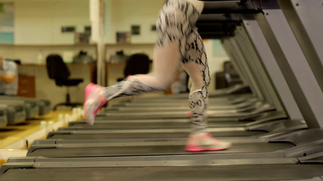 vídeos y material grabado en eventos de stock de la niña corre en una caminadora en el gimnasio. concepto de fitness. close-up. - sudadera