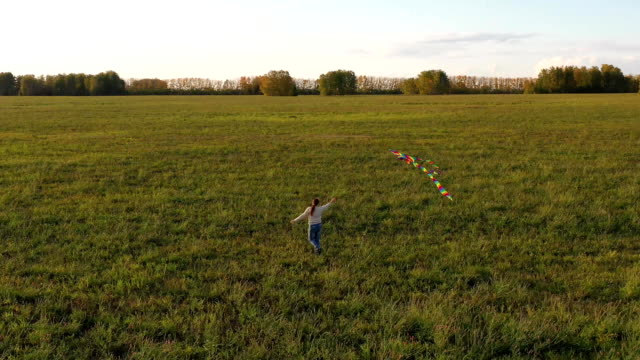 The girl runs with a kite on a green field. Laughter and joy, festive mood. summer holiday