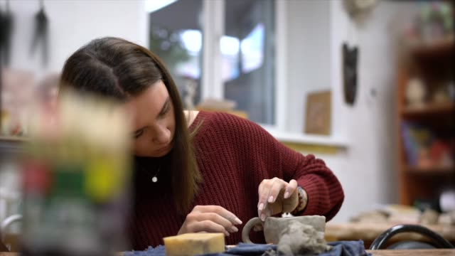 The girl sculpts a mug from clay