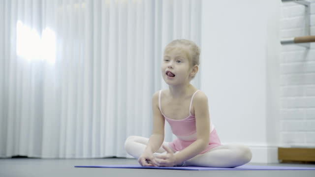 The girl sits cross-legged on the mat during the ballet class and stretches video