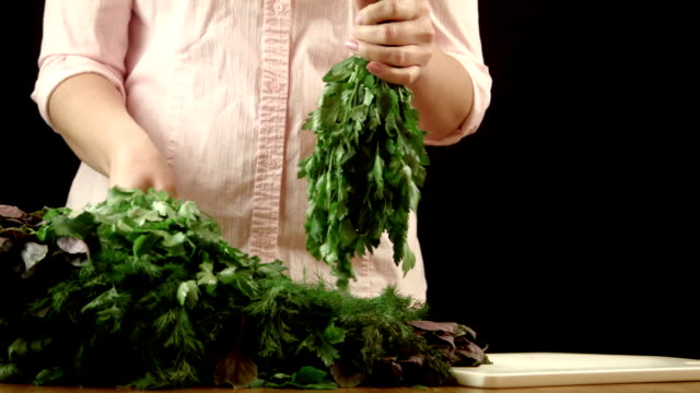 The girl sorts herbs The girl sorts parsley fennel and a basil, and puts them in bunches lip balm stock videos & royalty-free footage
