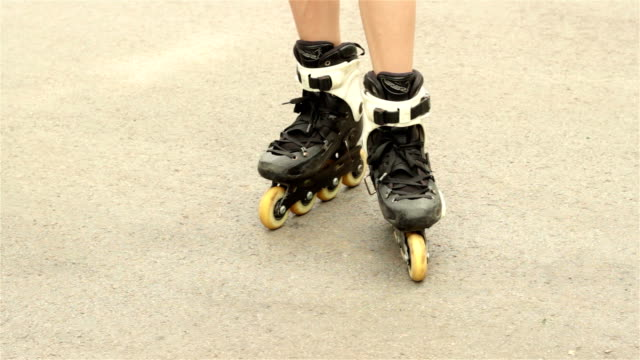 the girl stands on rollers and moving legs the girl stands on rollers on the pavement and moving legs charming stock videos & royalty-free footage