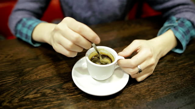 the girl stirs sugar in a cup of coffee in a family cafe. female hands closeup with cup of espresso of americano - espresso filmów i materiałów b-roll