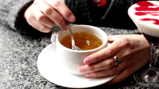The girl stirs sugar in a white mug. Female hands closeup with a cup of tea. video