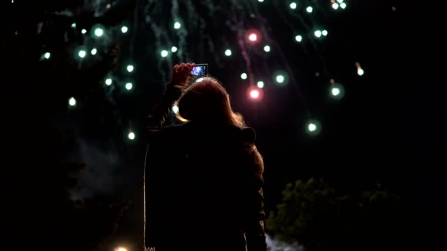 The girl takes pictures of fireworks on a mobile phone. Silhouette on the background of the sky illuminated by lights The girl takes pictures of fireworks on a mobile phone. Silhouette on the background of the sky illuminated by lights. fireworks stock videos & royalty-free footage