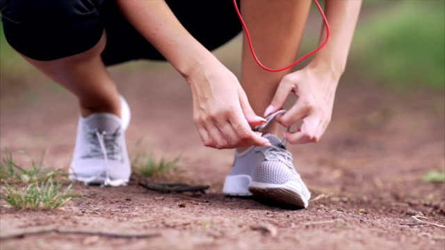 The girl ties up the shoelaces of the sneakers. The girl ties up the shoelaces of the sneakers close-up in the park. shoe stock videos & royalty-free footage