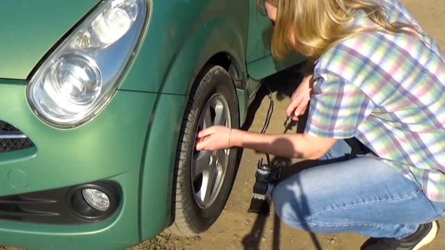 The girl unscrews the nipple on the car wheel and connects the hose from the air pump. Inflating and repairing a car wheel. A woman in a broken car video