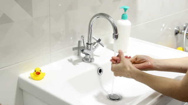 The girl washes her hands thoroughly with soap. Protect from virus
