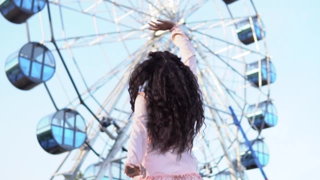 the girl waving her friends who are on the ferris wheel. slow motion - колесо обозрения стоковые видео и кадры b-roll