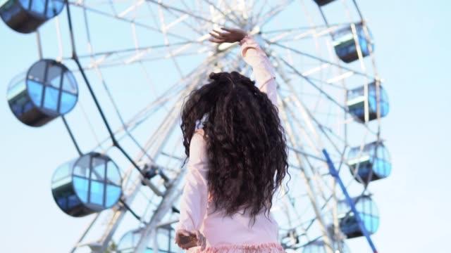 vídeos y material grabado en eventos de stock de la niña saludando a sus amigos que están en la rueda de la fortuna. cámara lenta - noria