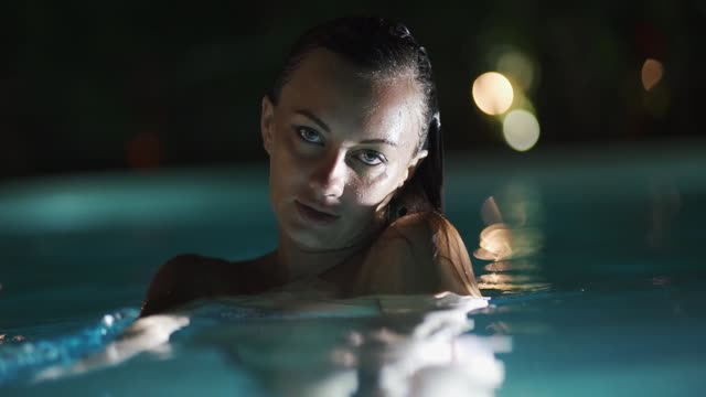 The girl with beautiful eyes in the evening in the pool Looking at camera. The girl with beautiful eyes in the evening in the pool Looking at camera. slow mo bikini stock videos & royalty-free footage