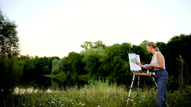 The girl with enthusiasm draws paints on a paper a landscape video