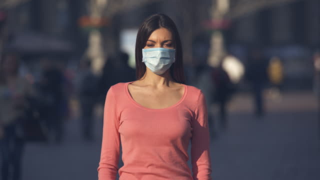 the girl with medical face mask stands in a crowded street - covid stock videos & royalty-free footage