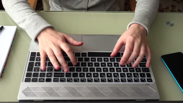 The girl working at home office hands on keyboard.