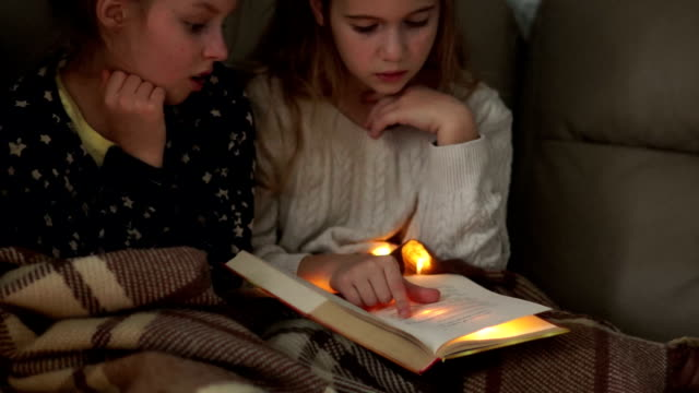 The girls had a pajama party. Sisters read a book and discuss their content. Christmas lights The girls had a pajama party. Sisters read a book and discuss their content. Christmas lights cousin stock videos & royalty-free footage