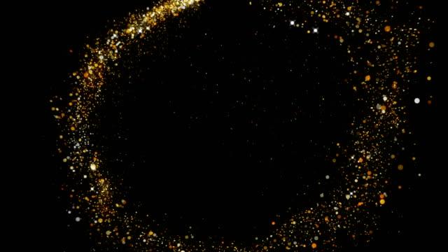 il bagliore e il volo di una stella brillante con la diffusione di spangles rotondi dorati su uno sfondo nero 4k - fascino video stock e b–roll