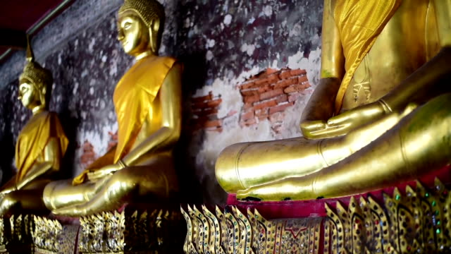 the golden buddha statue at the temple in thailand. - buddha video stock e b–roll