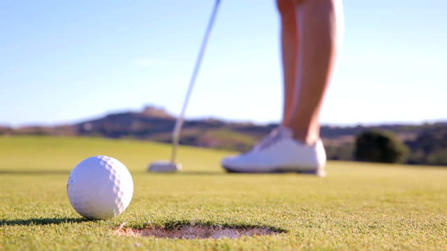 the golfer is trying to get the ball in the hole. unsuccessful kick. close up - парагвай стоковые видео и кадры b-roll