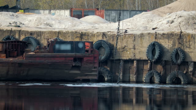The grab bucket of the excavator sinks into the river at the port against the background of an old, rusty, vintage barge and car tires