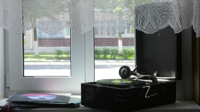 vídeos y material grabado en eventos de stock de el gramófono está parada en el alféizar de la ventana. antiguo gramófono con placa o vinilo disco en caja de madera. latón antiguo tocadiscos. gramófono con altavoz de bocina. concepto de entretenimiento retro. - disco audio analógico