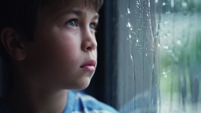 The gray weather makes him gloomy 4k video footage of a sad young boy watching the rain through a window at home one boy only stock videos & royalty-free footage
