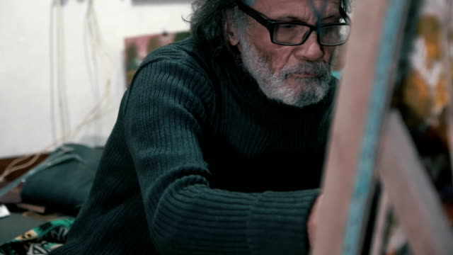 The gray-haired artist paints a picture (Close-up) video