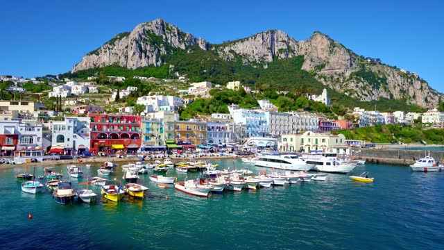 The green mountains and tourists on the coast of Capri, Italy