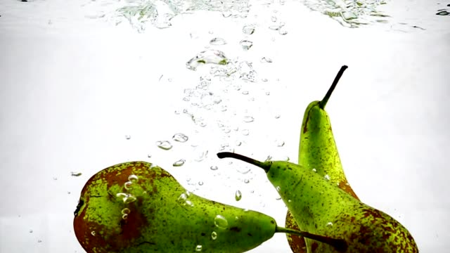 The green pear sinks into the water with bubbles on isolated white background. Video recording of pears in slow motion. Video recording of pears in slow motion. The green pear sinks into the water with bubbles on isolated white background. Theme of vegetarianism and raw food as a lifestyle. Fruit cocktail. pear stock videos & royalty-free footage