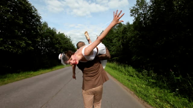 The Groom Carries the Bride on her Shoulder Along the Road video