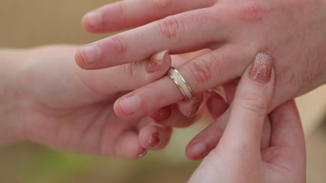 the groom places the ring on the bride's hand in wedding ceremony. - mano donna dita unite video stock e b–roll