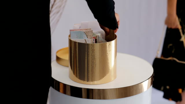 The Guest puts the envelope with money inside into basket with money gifts for gromm and bride. Beautiful golden cone shape box full of envelopes with money