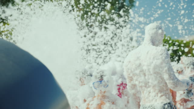 the gun fires the streams of foam on the crowd of tourists. foam party on the beach - gommapiuma video stock e b–roll