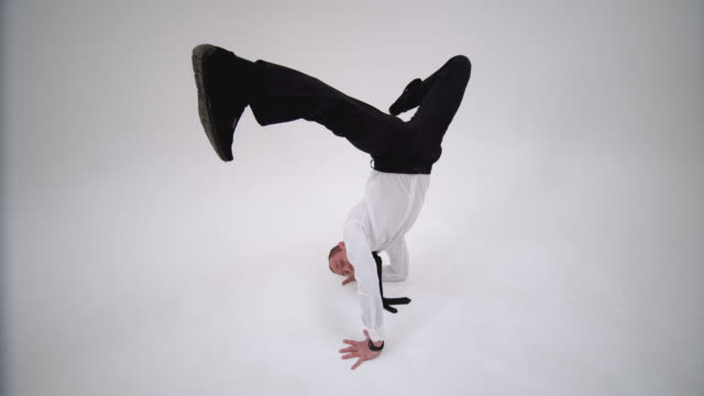 The guy dances a dance from a video game and stands on his hands with his legs spread. A cheerful office worker is dancing a break dance. The businessman stands on one hand spreading his legs