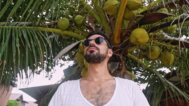 Le gars dans le T-shirt blanc se dresse sous un palmier. - Vidéo
