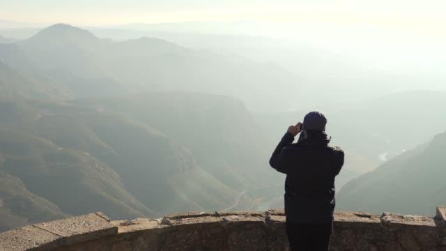 stockvideo's en b-roll-footage met de man op het observatie dek kijkt met een prachtig uitzicht op de bergen in de haze en nemen van foto 's - klooster
