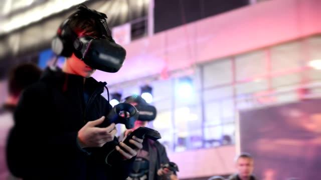 vídeos de stock, filmes e b-roll de o cara jogar jogo em realidade virtual vr fone de ouvido em um eventos de reunião. - realidade virtual