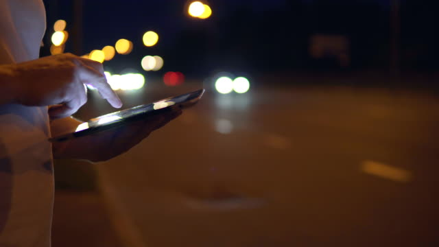 The guy uses the tablet in the city at night against the background of passing cars