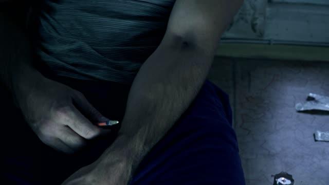 stockvideo's en b-roll-footage met de man die is verslaafd aan drugs, zit op de vloer en de volgende dosis injecteert met een spuit. - amfetamine