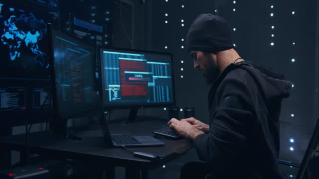 The hacker is in a dark room. There are three monitors in front of it and a large server in the background. The hacker constantly turns around, he is afraid that he is being pursued. The hacker is in a dark room. There are three monitors in front of it and a large server in the background. The hacker constantly turns around, he is afraid that he is being pursued. russian ethnicity stock videos & royalty-free footage