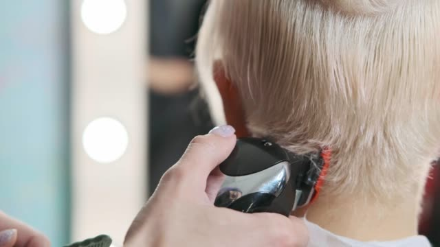 The hairdresser cuts blonde female client with a trimmer. A short pixie haircut and shaved temples . The hairdresser cuts blonde female client with a trimmer. A short pixie haircut and shaved temples . Ornament on the hair. short length stock videos & royalty-free footage