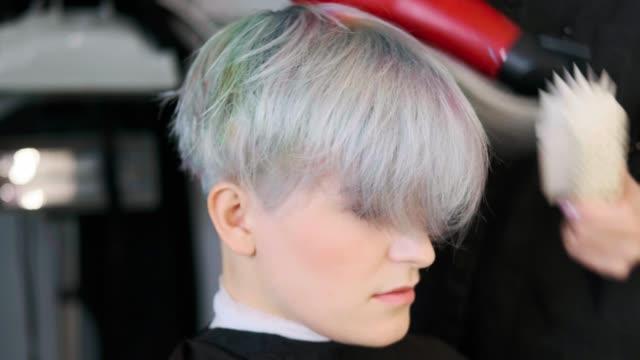 stockvideo's en b-roll-footage met de kapper droogt de föhn van het gekleurde haar van een vrouw. - roze haar