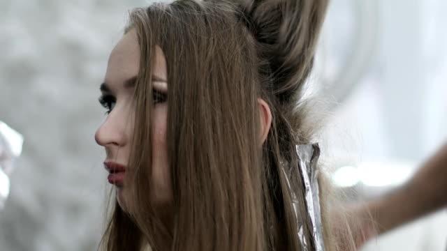 der friseur stylist arbeiten mit weiblichen lange braune haare. - haartönung stock-videos und b-roll-filmmaterial