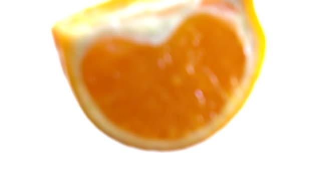 The half of juicy orange drops in fresh white milk slow motion video