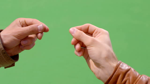 The hand acts: takes, holds, transfers to the other hand, catches, hold down A man's hand in a brown leather jacket on a green chromakey performs actions: takes, holds, transfers to the other hand, catches, hold down pinching stock videos & royalty-free footage