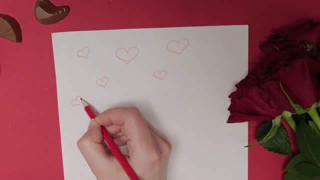 The hand draws hearts on paper with a pencil. There are roses and chocolates.